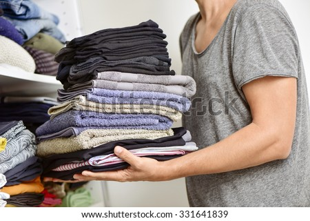 closeup of a young man carrying a pile of different folded clothes - stock photo