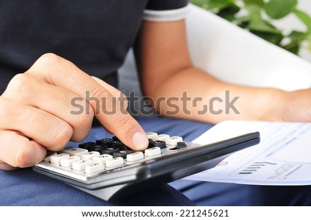 closeup of a young man checking a bill, a budget or a payroll with a calculator - stock photo