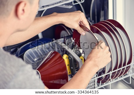 closeup of a young man introducing or taking out a plate into a dishwashing machine - stock photo