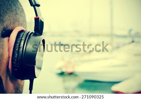 closeup of a young man listening to music with headphones in front of the sea in a marina, with a filter effect - stock photo