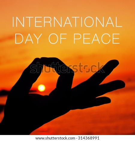 closeup of a young man meditating with his hands in gyan mudra at sunset and the text international day of peace - stock photo