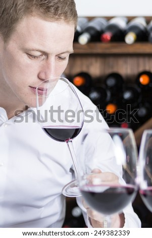 closeup of a young man on a wine tasting session on the olfactory phase with the wineglass in the nose is writing down in a wine tasting sheet at a restaurant - focus on the man face