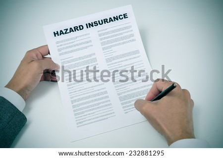 closeup of a young man signing a hazard insurance policy - stock photo