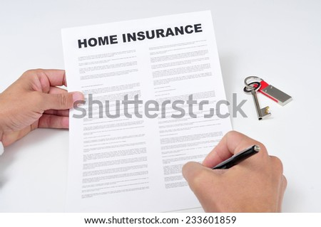 closeup of a young man signing a home insurance policy - stock photo