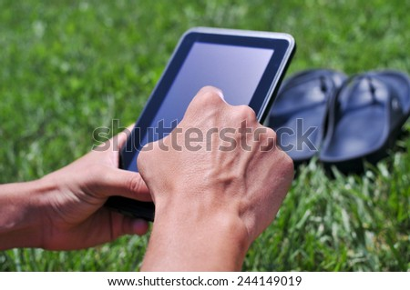 closeup of a young man using a tablet computer in a park or a garden - stock photo