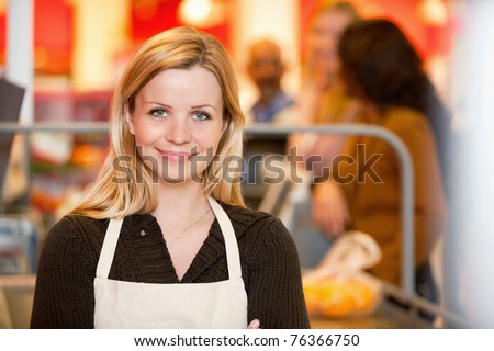 Closeup of a young shop assistant with customer in the background - stock photo