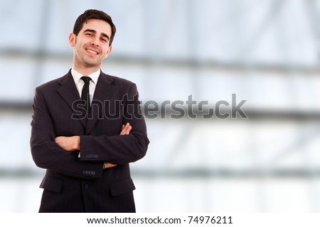 Closeup of a young smiling business man standing at a modern office - stock photo