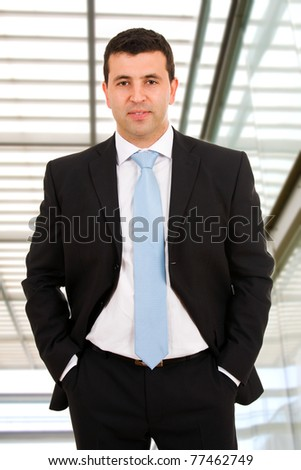 Closeup of a young smiling business man standing at a modern office building