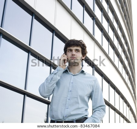 Closeup of a young smiling business man standing at a modern office, talking on phone