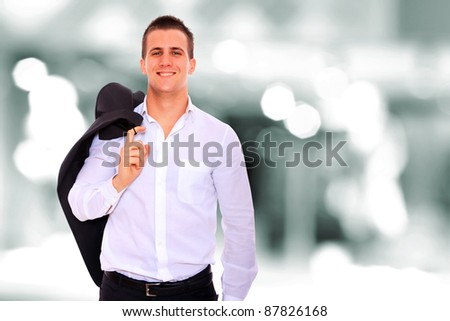 Closeup of a young smiling business man standing in a light and mordern business environement - stock photo