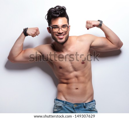 closeup of a young topless man showing off with his worked muscles and smiling to the camera. on light gray background - stock photo