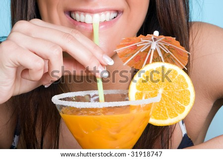 Closeup of a young woman drinking an orange cocktail - stock photo