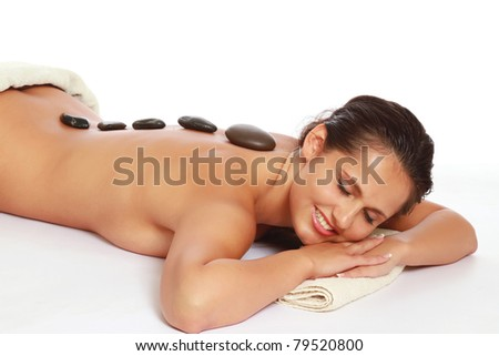 Closeup of a young woman getting spa treatment, focus on her back, isolated on white - stock photo