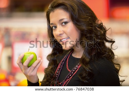 Closeup of a young woman holding apple in the supermarket - stock photo