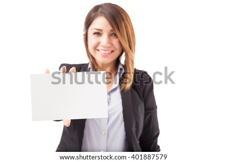 Closeup of a young woman in a suit holding up a sign in her hand. Focus on the sign, woman blurred. - stock photo