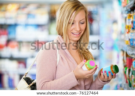 Closeup of a young woman smiling while holding jar in the supermarket - stock photo