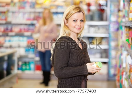 Closeup of a young woman smiling while shopping in the supermarket - stock photo