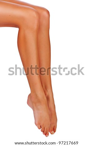 Closeup of a young woman tanned legs on white studio background - stock photo