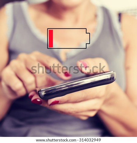 closeup of a young woman using a smartphone and an illustration of a low battery - stock photo