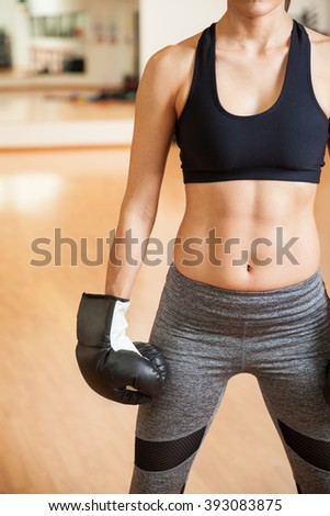 Closeup of a young woman with toned abs wearing boxing gloves in a gym. With some copy space on the side - stock photo