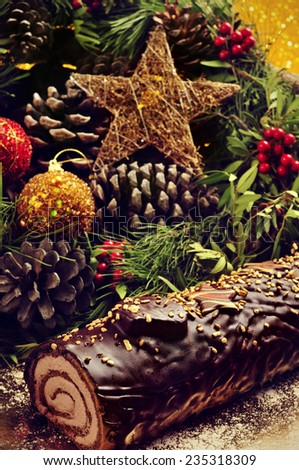 closeup of a yule log cake, traditional of christmas time, on a table ornamented with christmas balls and satrs, and natural ornaments - stock photo