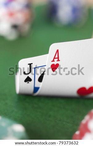 Closeup of Ace Jack hand with poker chips in background. - stock photo