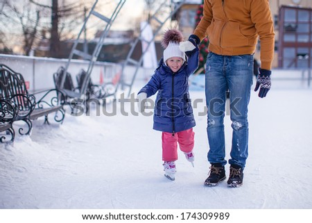 Closeup of adorable little girl with young dad on skating rink - stock photo