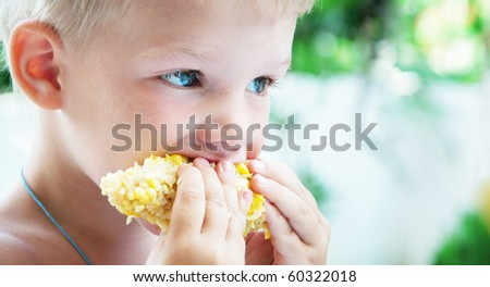 Closeup of adorable 3 years old child eating sweet corn - stock photo