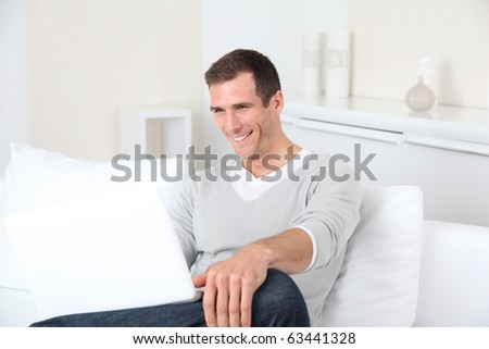 Closeup of adult man sitting on sofa with laptop computer - stock photo