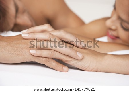 Closeup of affectionate couple holding hands in bed - stock photo