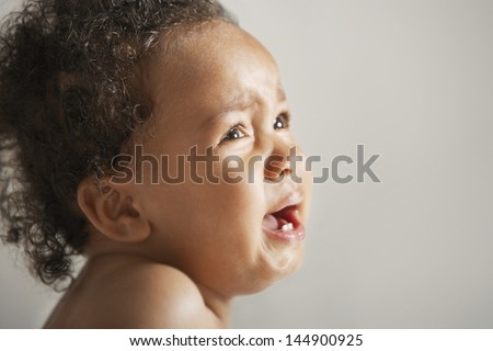 Closeup of African American baby crying isolated on colored background - stock photo
