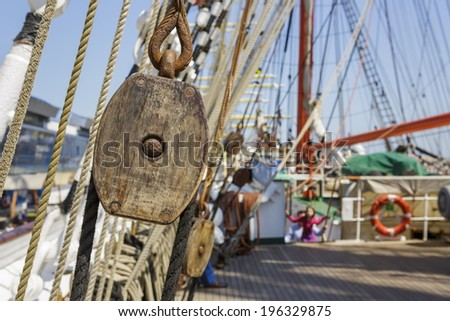 Closeup of aged vintage marine ropes and wooden tackle block on the deck of an old sailing vessel. - stock photo