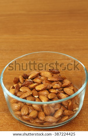 Closeup of almonds coated with baked on maple syrup in a clear glass bowl on an oak wood table top. Healthy and sweet almond nuts coated with baked on maple syrup. - stock photo