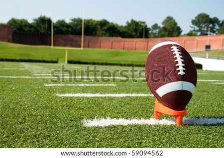 Closeup of American football on tee with goal post in background - stock photo