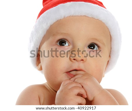 Closeup of an adorable baby boy in Santa's hat with the wonder of Christmas in his eyes.  Isolated on white. - stock photo