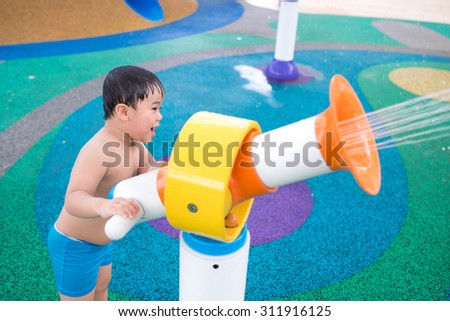 Closeup of an adorable child playing with toy in water park. Outdoor shot - stock photo
