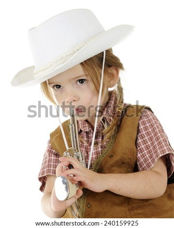Closeup of an adorable preschool cowgirl pretending to blow smoke of the end of the toy gun she hold.  On a white background.  - stock photo