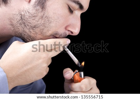 Closeup of an adult man (30 years old) with his profile to the camera, concentrated in lighting a marijuana spliff (aka reefer; joint). Isolated on black background. - stock photo
