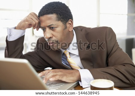 Closeup of an African American businessman using laptop with hand on head - stock photo