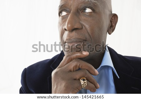 Closeup of an African American senior businessman with hand on chin against white background - stock photo