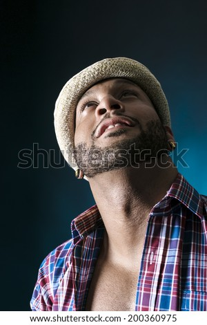 Closeup of an African American young man in hat looking up. Copy space - stock photo