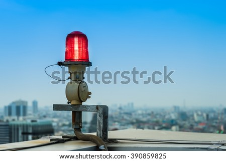Closeup of an aircraft warning light on top of a highrise of building in evening time - stock photo