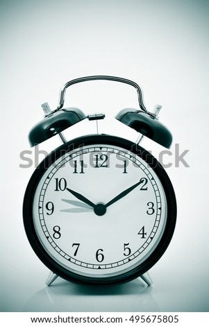 closeup of an alarm clock adjusting backward one hour at the end of the summer, with a vignette added