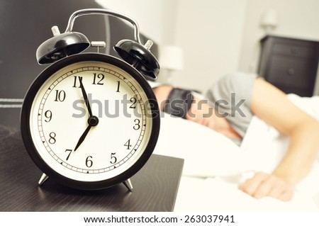 closeup of an alarm clock at 6.55 in the morning on the night table and a young caucasian man sleeping in bed with a black sleep mask - stock photo