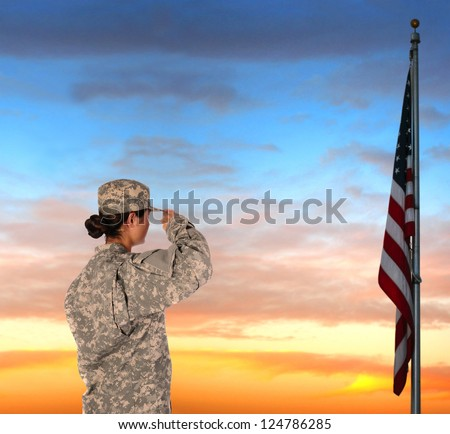 Closeup of an American Female Soldier in combat uniform saluting a flag at sunset. - stock photo