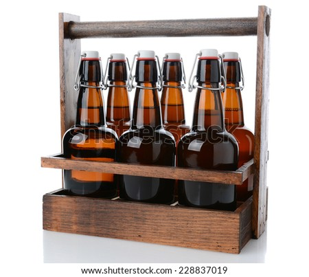 Closeup of an antique wooden six pack beer carrier with swing top beer bottles on a white background with reflection.  - stock photo