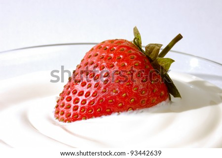 Closeup of an appetizing strawberry in cream - stock photo