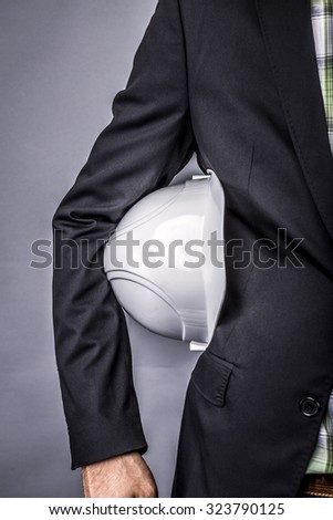 Closeup of an  architect holding white hardhat under his arm isolated over gray background - stock photo