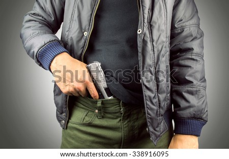 closeup of an armed terrorist with gray background - stock photo