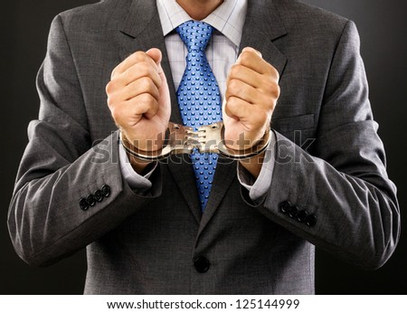 Closeup  of an arrested man with  handcuffs on grey - stock photo